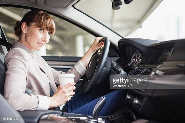 Germany, Hesse, Frankfurt, portrait of smiling businesswoman driving car with coffee to go in one hand