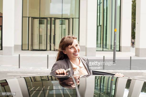 Germany, Hesse, Frankfurt, portrait of smiling businesswoman leaning on her car