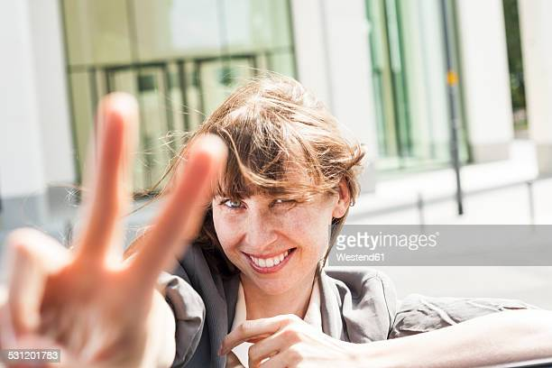 Germany, Hesse, Frankfurt, portrait of smiling businesswoman leaning on car roof showing victory-sign