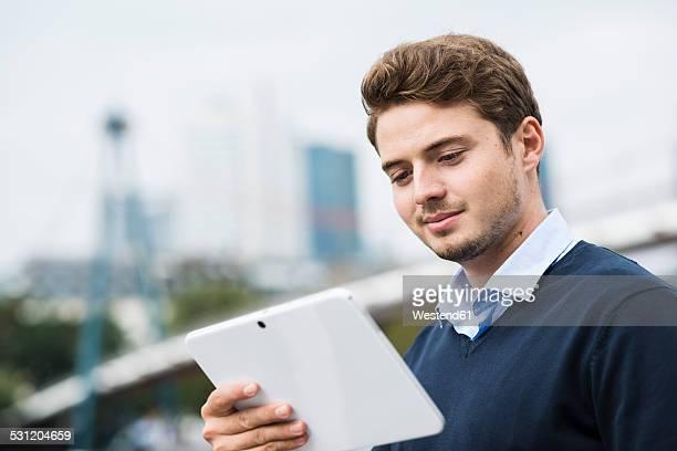 Germany, Hesse, Frankfurt, portrait of smiling young man using digital tablet