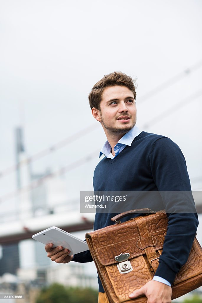 Germany, Hesse, Frankfurt, portrait of smiling young man with briefcase and digital tablet