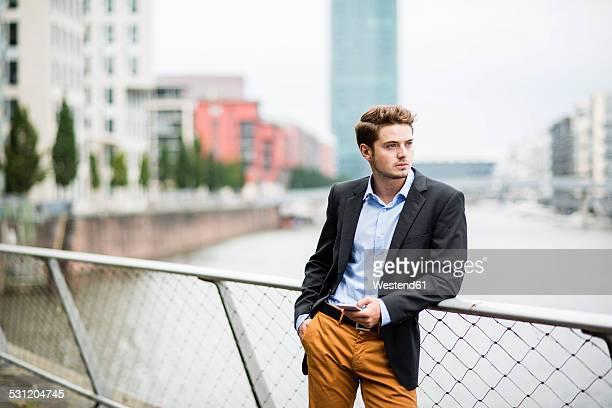 Germany, Hesse, Frankfurt, portrait of young businessman standing on a bridge