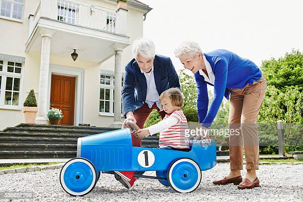 Germany, Hesse, Frankfurt, Senior couple with granddaughter sitting pedal car