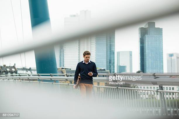 Germany, Hesse, Frankfurt, young businessman walking on a bridge using his smartphone