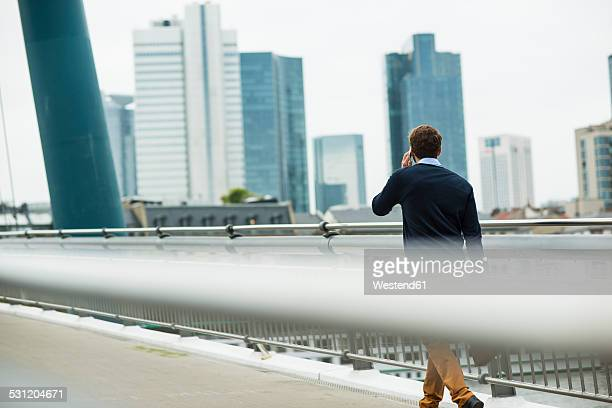 Germany, Hesse, Frankfurt, young businessman walking on a bridge telephoning with his smartphone