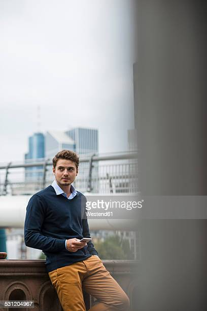 Germany, Hesse, Frankfurt, young man standing on a bridge with his smartphone