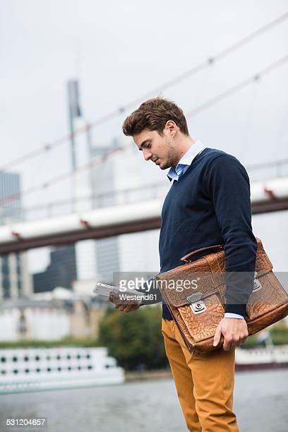 Germany, Hesse, Frankfurt, young man using digital tablet
