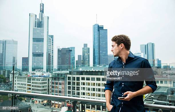 Germany, Hesse, Frankfurt, young man with his smartphone standing in front of the skyline