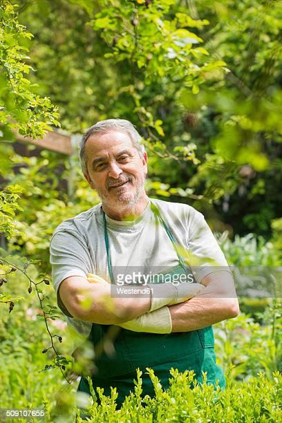 Germany, Hesse, Lampertheim, portrait of senior gardener with crossed arms