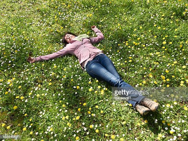 Germany, Hesse, Mature women lying on meadow