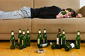 Germany, Hessen, Frankfurt, Drunk man lying on sofa with empty beer bottles