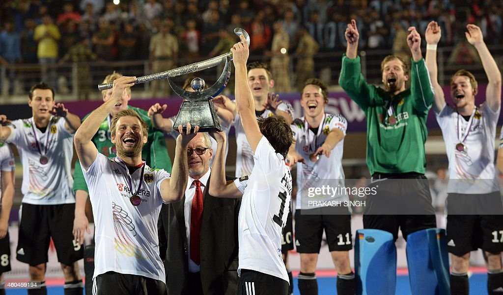Germany hockey team captain Moritz Furste lifts the trophy as teammates cheer on December 14 2014 after defeating Pakistan during their Hero Hockey...