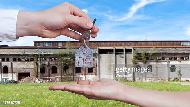 Germany, Human hands exchanging house key in front of very old and broken down factory building