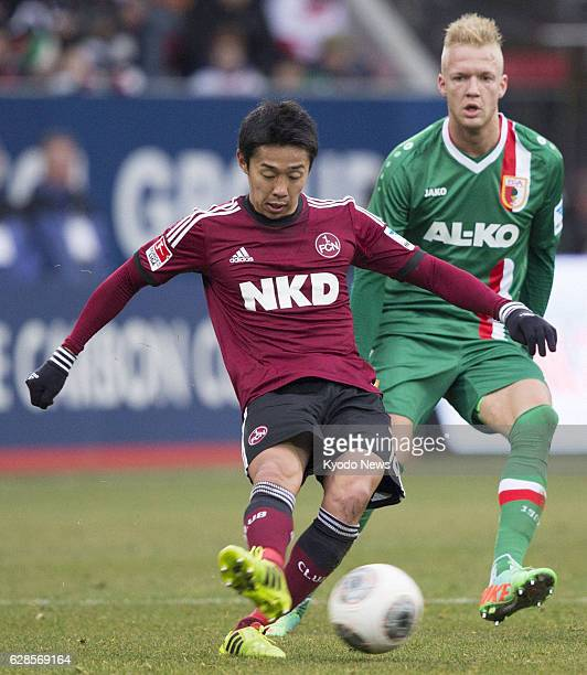 AUGSBURG Germany Japan midfielder Hiroshi Kiyotake of Nuremberg passes the soccer ball as Augsburg midfielder Kevin Vogt gives pursuit during a...