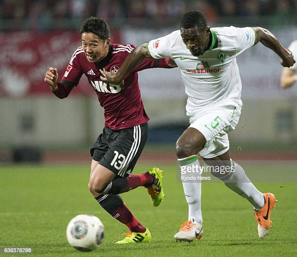 NUREMBERG Germany Japanese footballer Hiroshi Kiyotake of Nuremberg and Werder Bremen's Assani Lukimya compete for the ball in a Bundesliga game in...