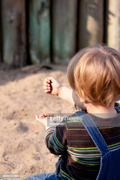 Germany, Kiel, girl plays with sand on playground, from behind