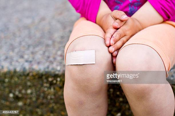 Germany, Kiel, Girl with patch on knee, close up