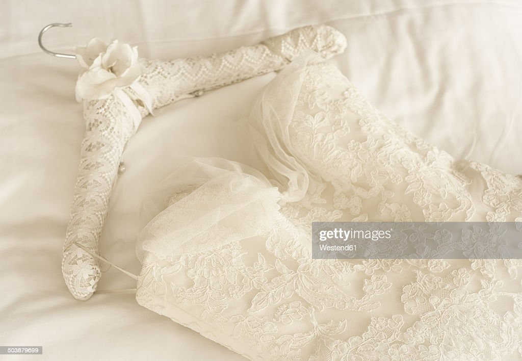 Germany, Lace wedding dress lying on bed