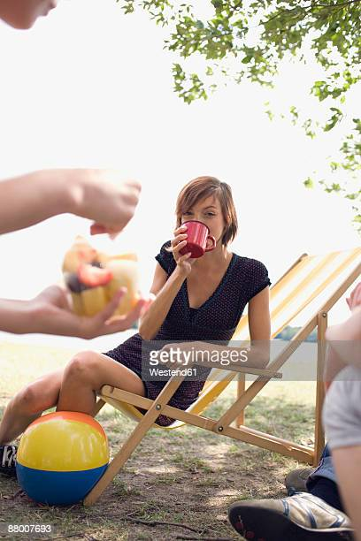 Germany, Leipzig, Ammelshainer See, friends having picnic, woman sitting on chair drinking from mug