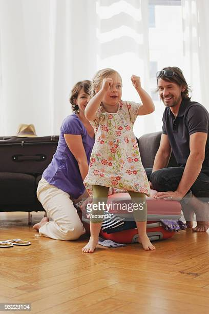 Germany, Leipzig, Parents packing suitcase, girl (4-5) dancing