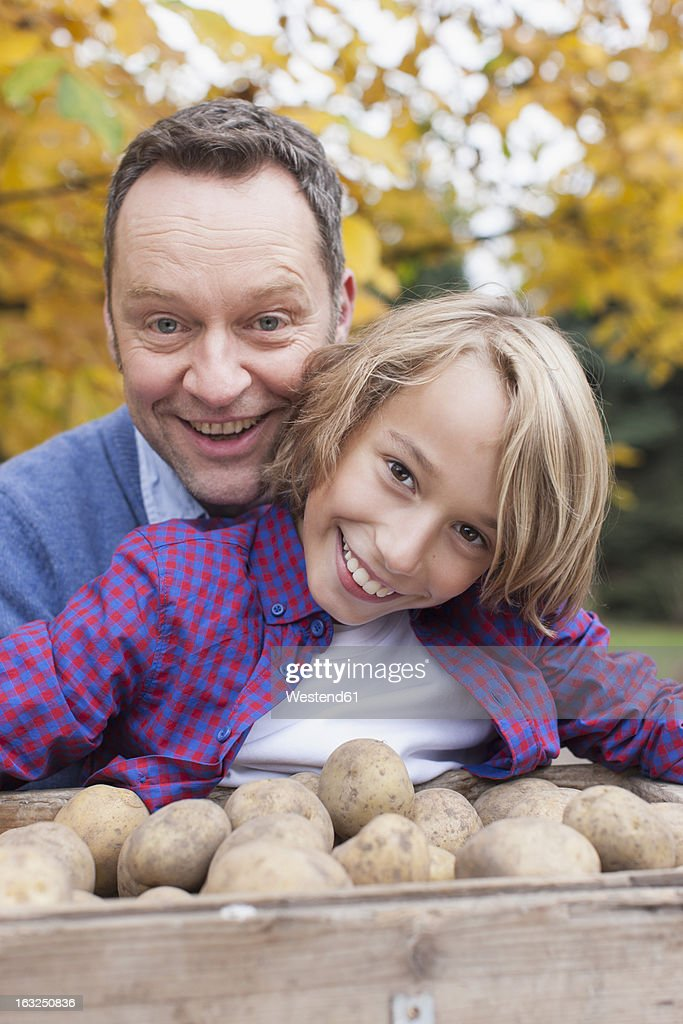 Germany, Leipzig, Father and son collecting potatoes : Stock Photo