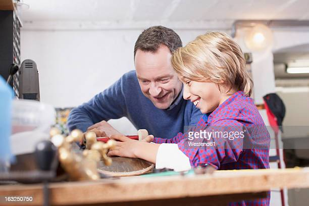 Germany, Leipzig, Father and son repairing skateboard