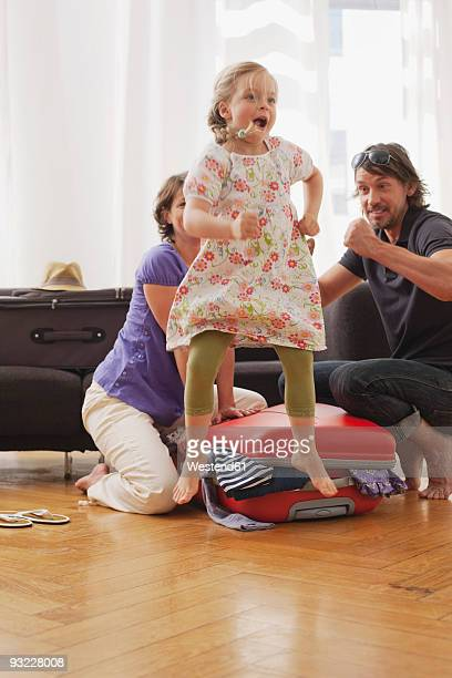 Germany, Leipzig, Girl (4-5) jumping, father and mother packing suitcase in background