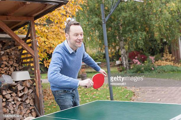 Germany, Leipzig, Mature man playing table tennis