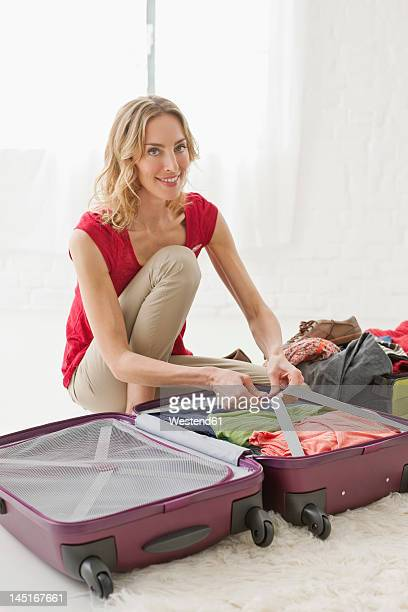 Germany, Leipzig, Mid adult woman packing suitcase, portrait