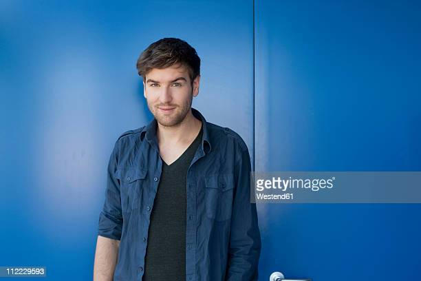 Germany, Leipzig, Young man standing, smiling, portrait