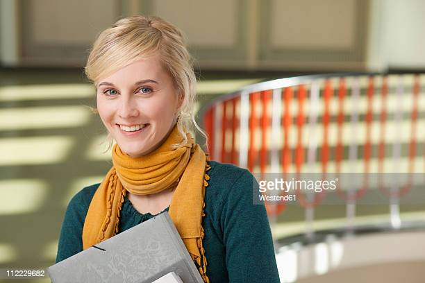 Germany, Leipzig, Young woman standing with books in hallway, smiling, portrait