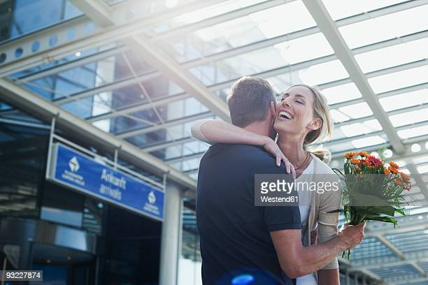 Germany, Leipzig-Halle, Couple embracing at airport, man holding flowers