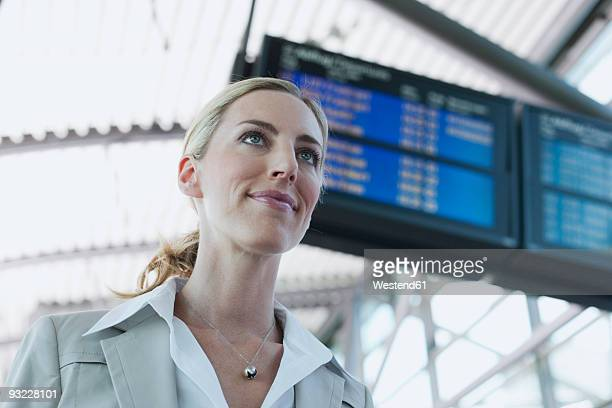 Germany, Leipzig-Halle, Young businesswoman at airport, smiling, low angle view