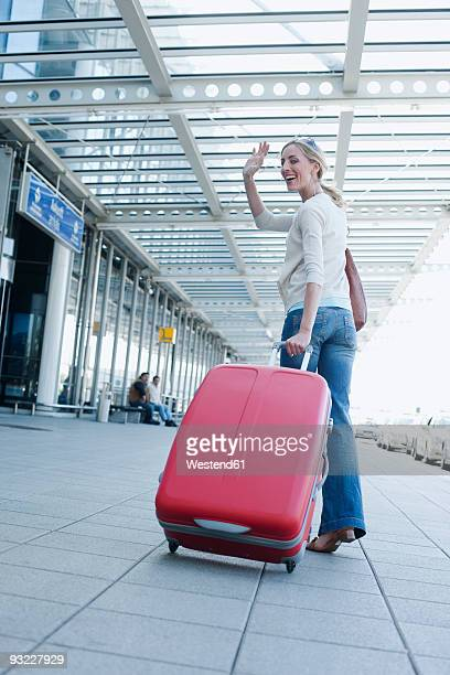 Germany, Leipzig-Halle, Young woman with suitcase at airport, smiling, waving