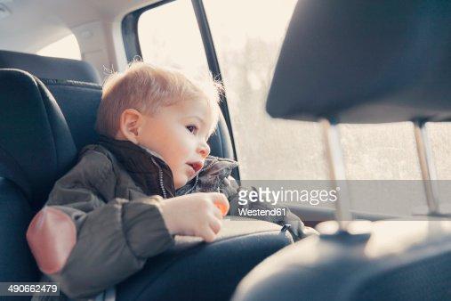 Germany, Little boy sitting in back-seat car seat