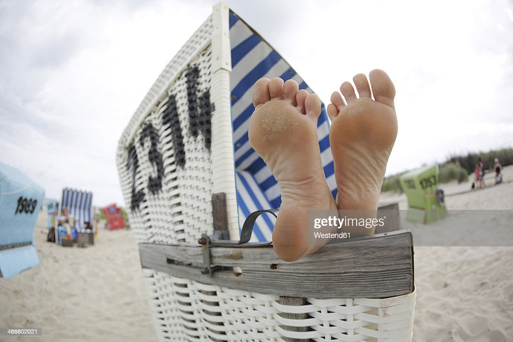Germany, Lower Saxony, East Frisia, Langeoog, feet on an armrest of a roofed wicker beach chair
