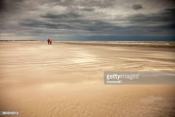 Germany, Lower Saxony, Eastern Friesland, Spiekeroog, couple having a walk at the low tide