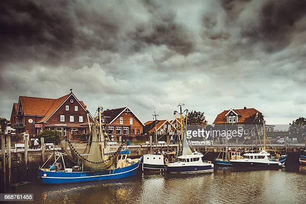 Germany, Lower Saxony, Greetsiel, Neuharlingersiel, fishing harbour and angry clouds