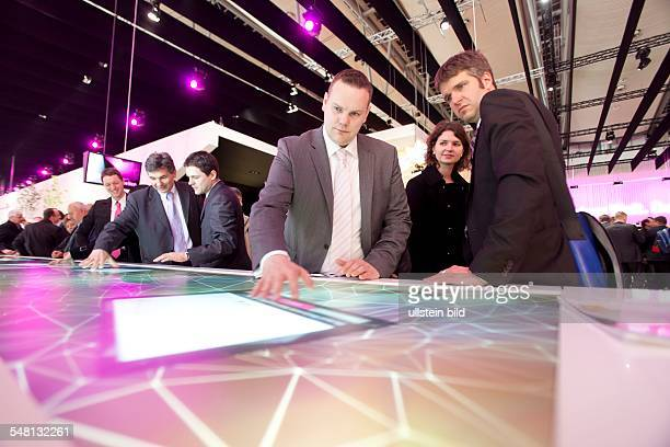 Germany Lower Saxony Hannover Visitors looking at overdeimensional touchscreens during the Cebit electronics fair