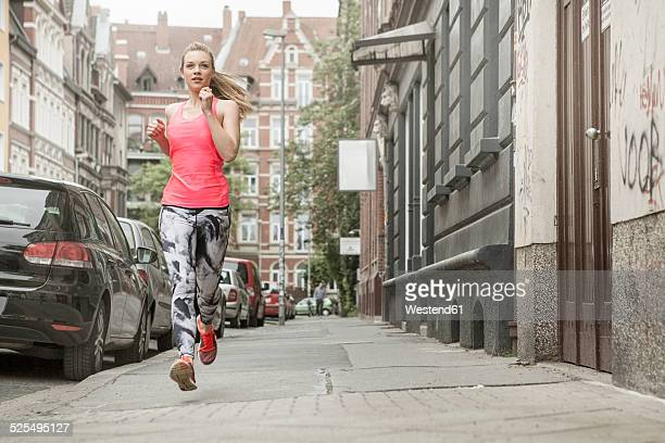 Germany, Lower Saxony, Hanover, young female jogger running on pavement