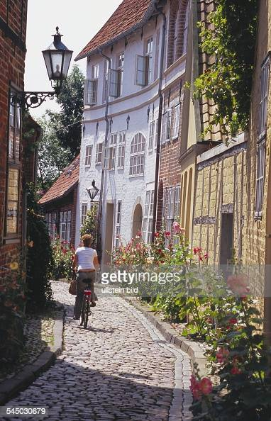 Germany Lower Saxony Lueneburg Cyclist in the cobblestone paved alleyway 'In der Techt' with halftimbered and bricklined houses