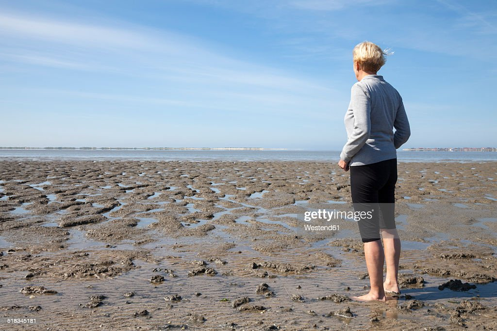 Germany, Lower Saxony, Nessmersiel, woman looking at wadden sea