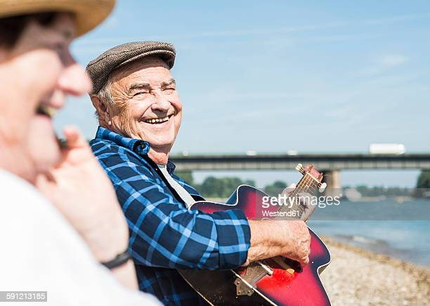 Germany, Ludwigshafen, portrait of laughing senior man with guitar at riverside