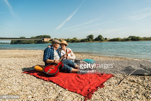 Germany, Ludwigshafen, senior couple relaxing with guitar on blanket on the beach
