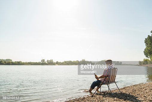 Germany, Ludwigshafen, senior man with beer bottle sitting on folding chair at riverside