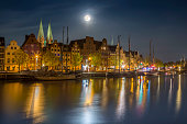 Germany, Luebeck, historic buildings at the Trave river at night