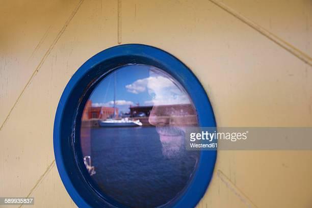 Germany, Luebeck, man behind porthole at harbor