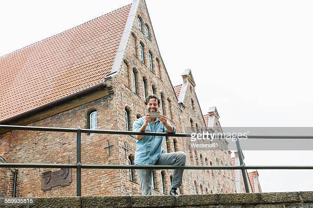 Germany, Luebeck, man with smartphone in the city