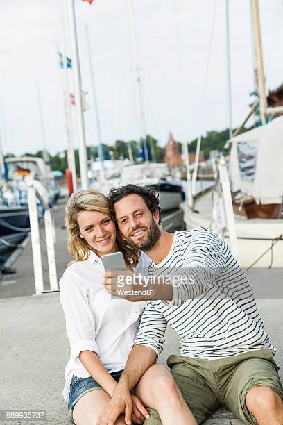 Germany, Luebeck, smiling couple at marina taking a selfie