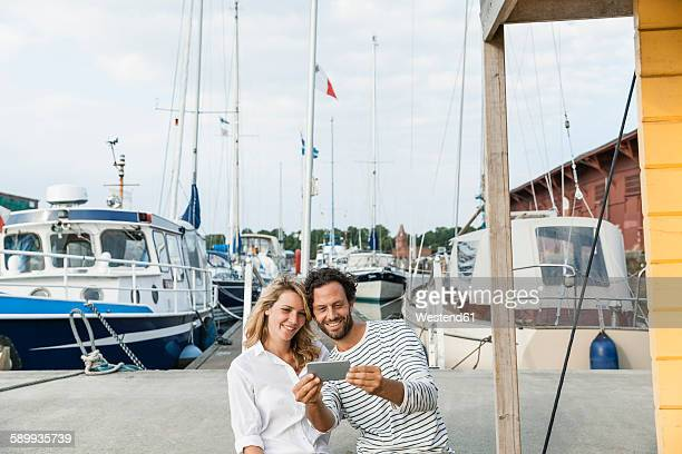 Germany, Luebeck, smiling couple at marina with smartphone